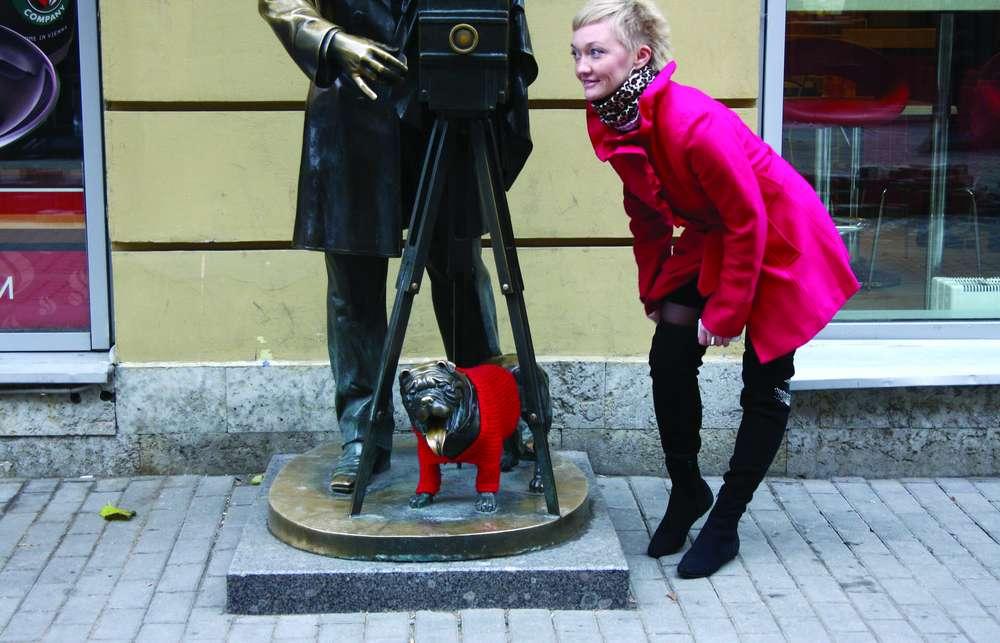 Собаке, которая сидит у ног памятника фотографу, одели вязаный джемпер. Памятник фотографу на Малой Садовой улице.
